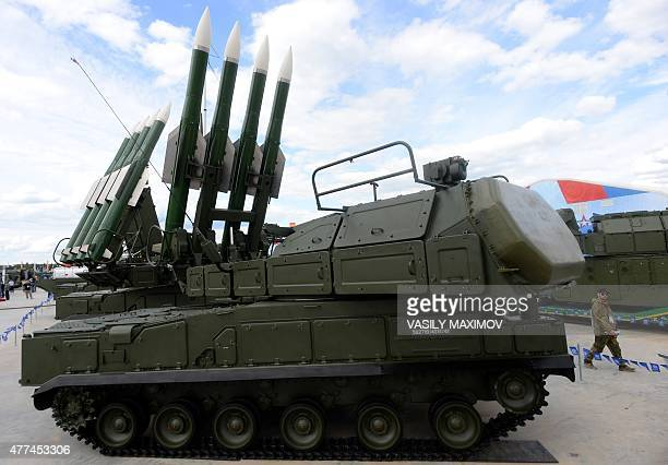 A visitor walks past a Russian selfpropelled surfacetoair missile systems BUKM2E during the 'Army2015' international military forum in Kubinka...