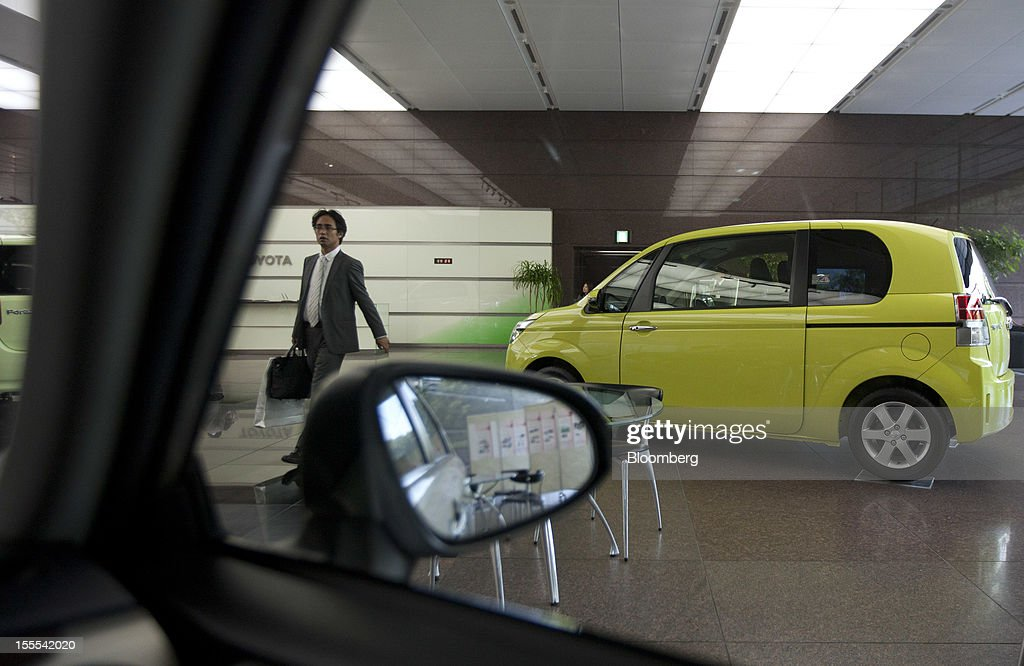 A visitor walks past a Toyota Motor Corp. Porte compact vehicle displayed at the company's head offices in Tokyo, Japan, on Monday, Nov. 5, 2012. Toyota Motor Corp., Asia's biggest carmaker, raised its full-year profit forecast as rising demand for the Prius hybrid in the U.S. and Japan helped make up for slumping sales in China. Photographer: Tomohiro Ohsumi/Bloomberg via Getty Images