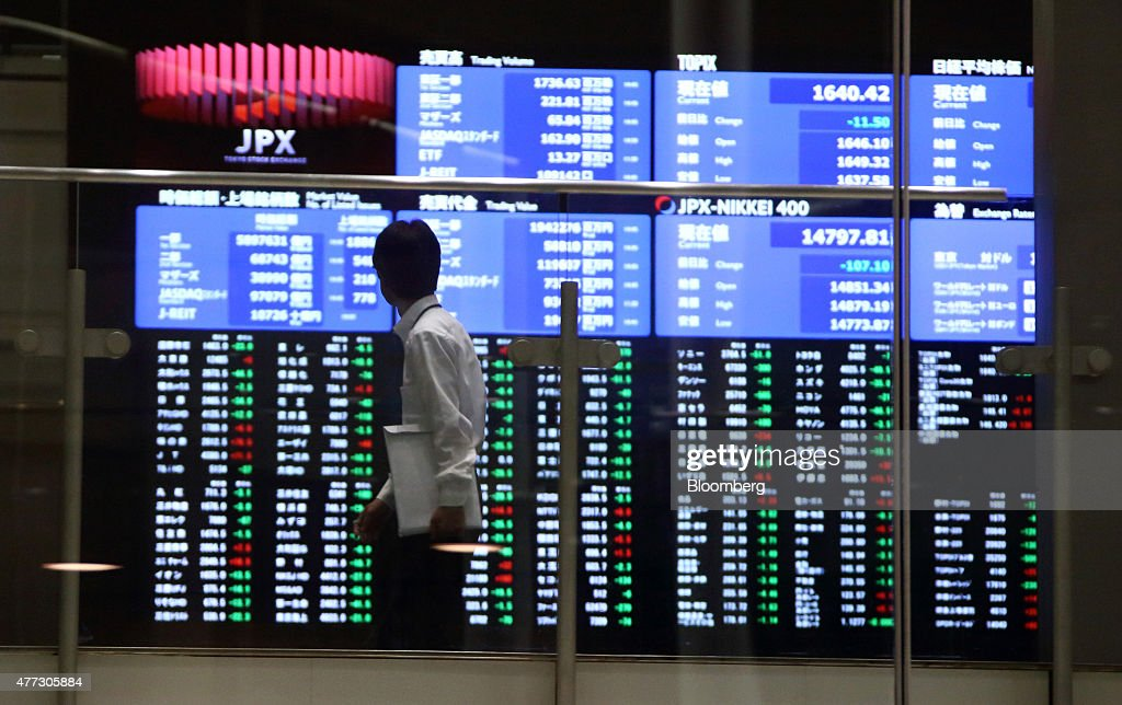 A visitor walks past an electric stock board at the Tokyo Stock Exchange operated by Japan Exchange Group Inc in Tokyo Japan on Tuesday June 16 2015...