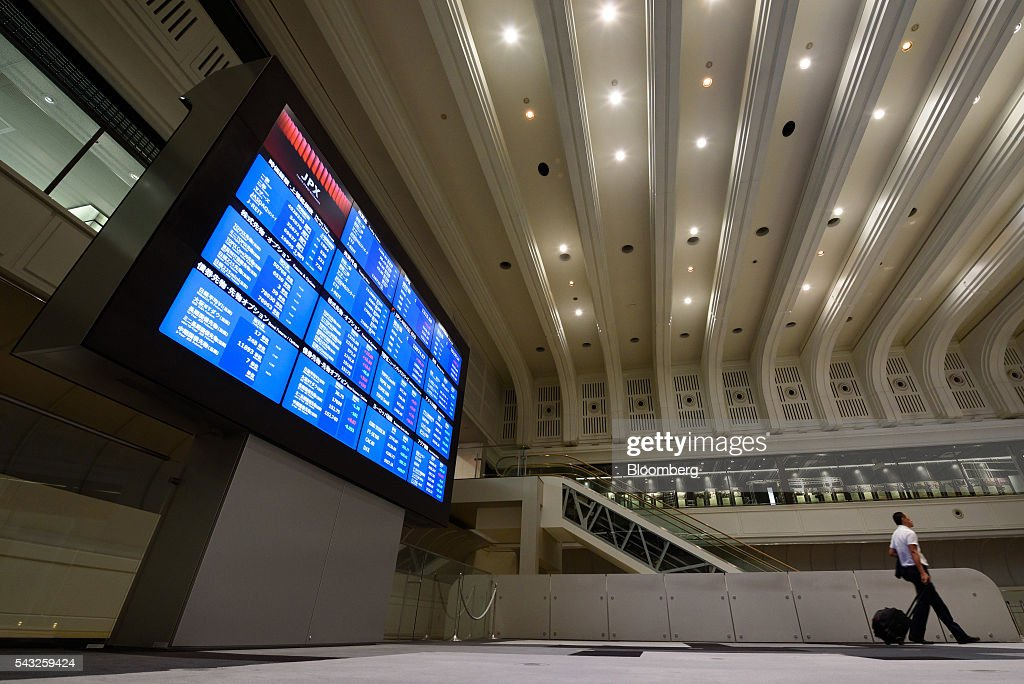 A visitor walks past an electronic board displaying market indices at the Tokyo Stock Exchange (TSE), operated by Japan Exchange Group Inc. (JPX), in Tokyo, Japan, on Monday, June 27, 2016. The yen was closing in on 99 per dollar at one point Friday and headed for its biggest gain since it was freely floated in February 1973, as Britain's vote to leave the European Union prompted investors to flee global markets and seek safety in Japanese government bonds. Photographer: Akio Kon/Bloomberg via Getty Images