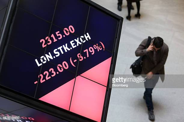 A visitor walks past an illuminated rotating cube displaying share price information for the London Stock Exchange as it stands in the atrium of the...