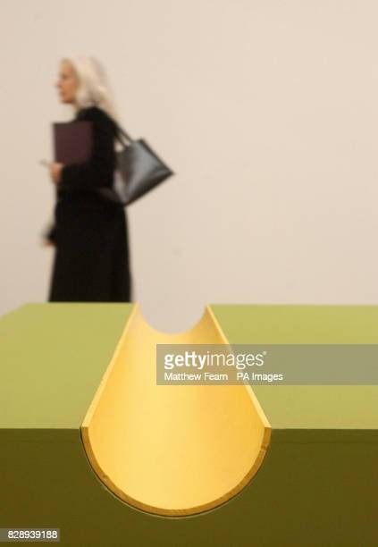 A visitor walks past an untitled oil on wood with iron pipe piece during the press preview of the Donald Judd Exhibition at London's Tate Modern