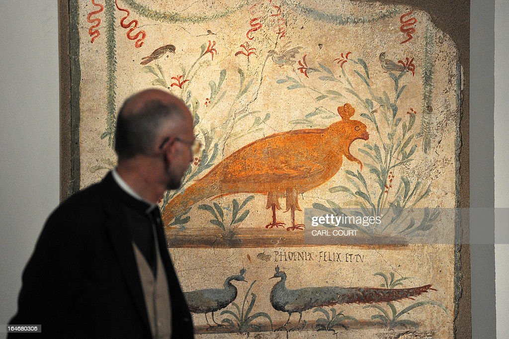 A visitor walks past fresco featuring a phoenix that was painted on the outside wall of a taverna in Pompeii, the Roman town that was partially destroyed in the eruption of Mount Vesuvius in AD 79, during the press preview for the 'Life and Death Pompeii and Herculaneum' exhibition at the British Museum in central London on March 26, 2013. Pompeii and Herculaneum were both devestated when the eruption of Vesuvius buried the towns in ash and pumice leaving many victims in situ. Preserved frescoes reveal details about 1st century Roman culture. AFP PHOTO / CARL COURT