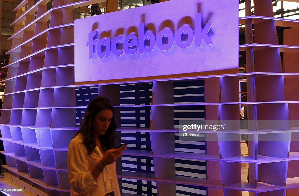 A visitor walks past in front of a Facebook logo during the Viva Technology show on June 30, 2016 in Paris, France. Viva Technology Startup Connect, the new international event brings together 5,000 startups with top investors, companies to grow businesses and all players in the digital transformation who shape the future of the internet.