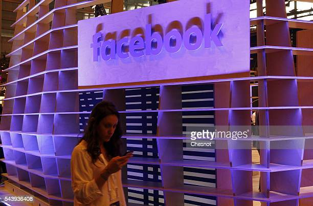 A visitor walks past in front of a Facebook logo during the Viva Technology show on June 30 2016 in Paris France Viva Technology Startup Connect the...