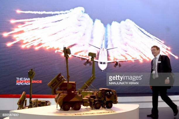 A visitor walks past material on the SAAB stand in the exhibition area on the third day of the 11th edition of 'Aero India' a biennial international...