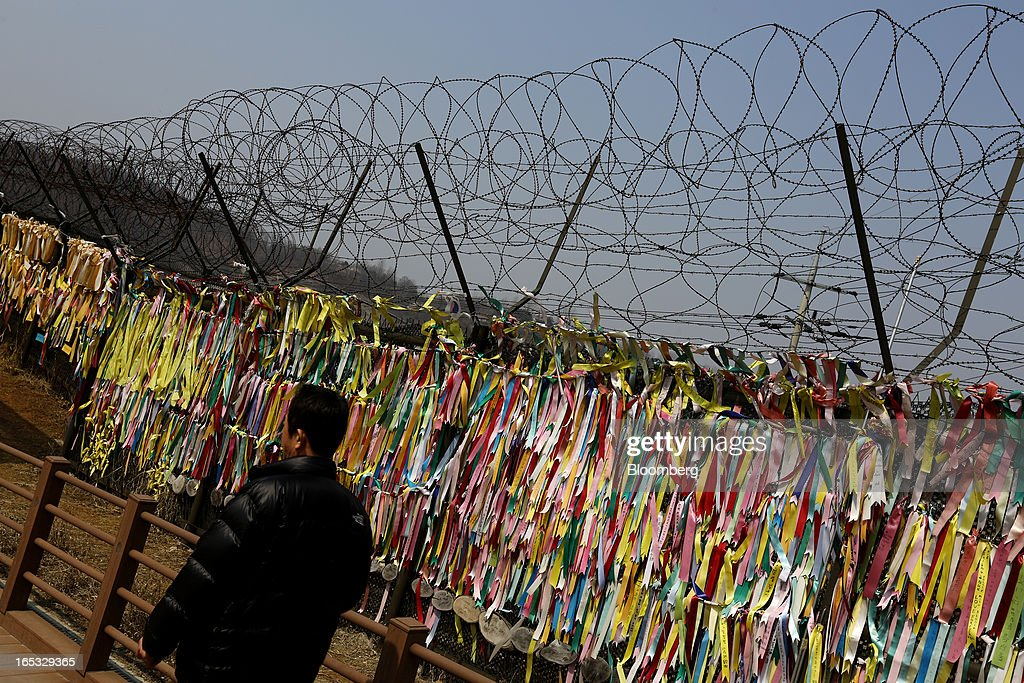 A visitor walks past ribbons hanging on a barbed-wire fence at the Imjingak pavilion near the demilitarized zone (DMZ) in Paju, South Korea, on Wednesday, April 3, 2013. North Korea prevented South Korean workers from entering a jointly run industrial park today, adding to tensions after saying it will restart a mothballed nuclear plant and threatening to attack its southern neighbor. Photographer: SeongJoon Cho/Bloomberg via Getty Images