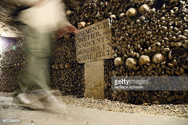 A visitor walks past skulls and bones from the defunct Holy Innocents' Cemetery now stacked at the Catacombs of Paris on October 14 2014 These...