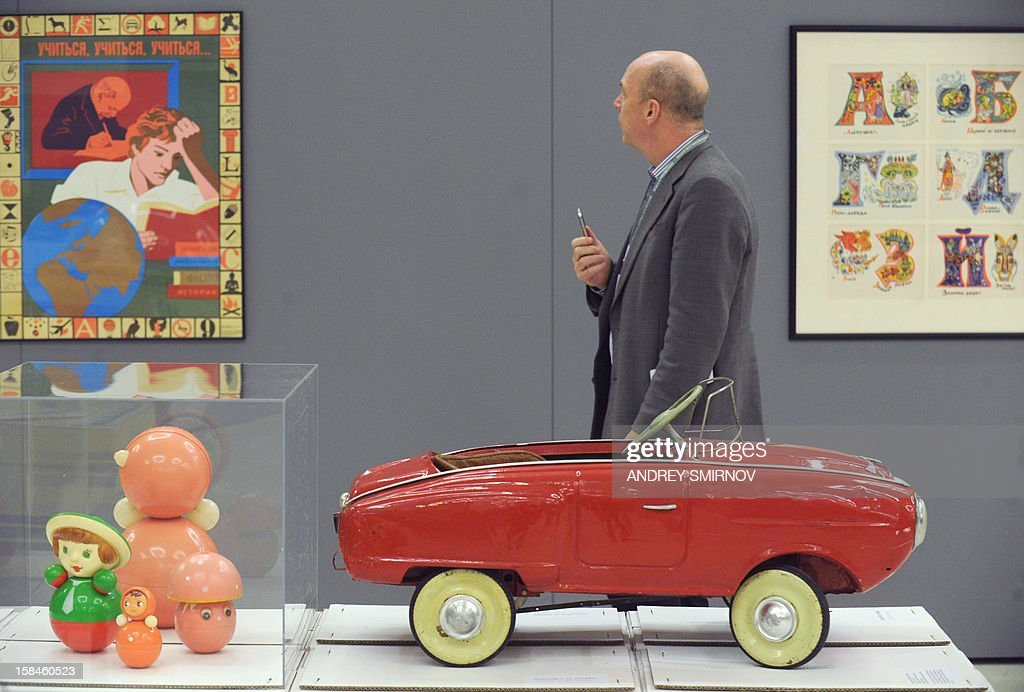 A visitor walks past Soviet-era toys, tilting dolls and a child's pedal car, displayed at the exhibition 'Soviet Design, 1950-1980,' in Moscow, on December 5, 2012. Toys, kitchen utensils, furniture, posters, clothes, cars ... more than 200 objects and creations of all kinds objects designed for everyday life in the Soviet Union in 1950-1980 have been patiently gathered, from Russian museums, ancient designers, private collectors or recovered from private individuals through the Internet.AFP PHOTO / ANDREY SMIRNOV