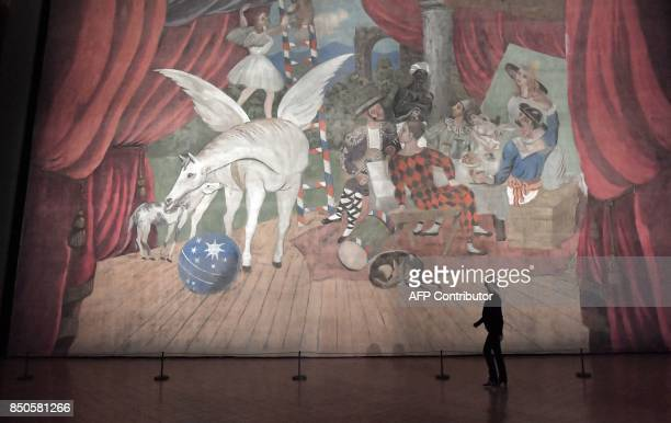 A visitor walks past the artwork a monumental stage curtain for the ballet 'Parade' by Spanish artist Pablo Picasso during the press preview of the...