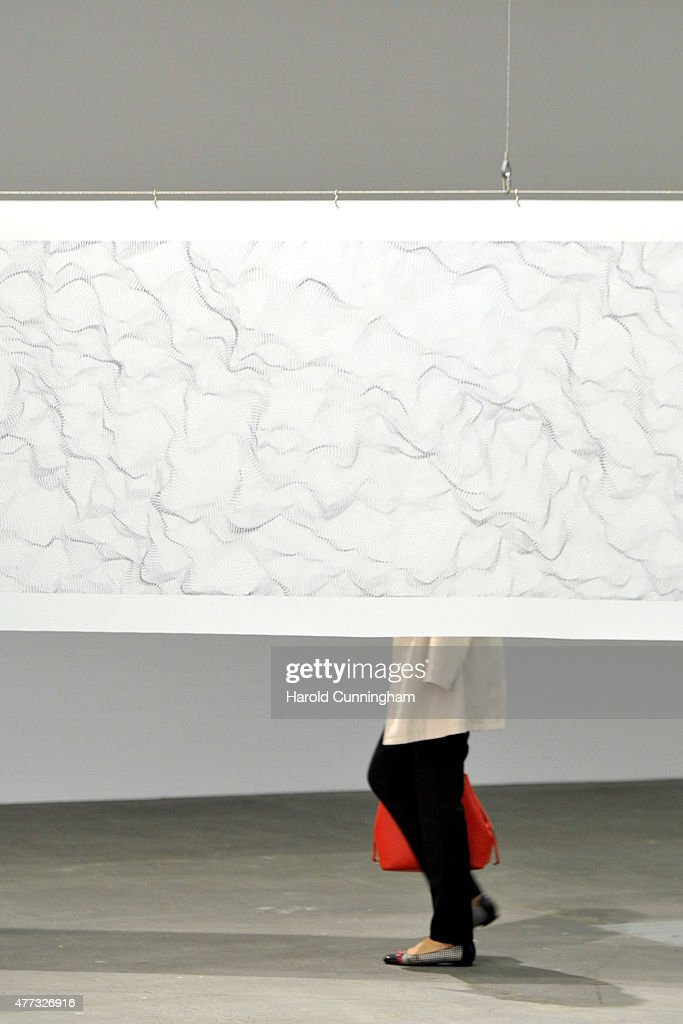 A visitor walks past the artwork ' Il movimento delle cose' by Dadamaino during Art Basel on June 16, 2015 in Basel, Switzerland. Art Basel one of the most prestigious art fair in the world, which runs until the 21th of June 2015 will showcase the work of more than 4,000 artists selected by 300 leading art galleries.