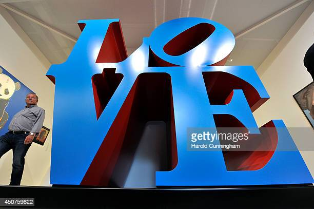 A visitor walks past the artwork 'LOVE blue/red' by Robert Indiana in the gallery section of Art Basel on June 17 2014 in Basel Switzerland Art Basel...