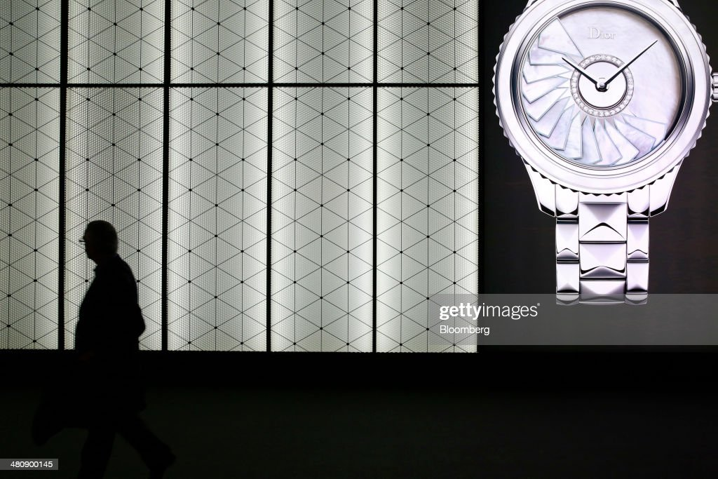 A visitor walks past the Christian Dior SA display booth during the Baselworld luxury watch and jewelry fair in Basel, Switzerland, on Thursday, March 27, 2014. Over 1,400 companies from the watch, jewelry and gem industries will display their latest innovations and products to more than 120,000 visitors at this year's luxury show. Photographer: Gianluca Colla/Bloomberg via Getty Images