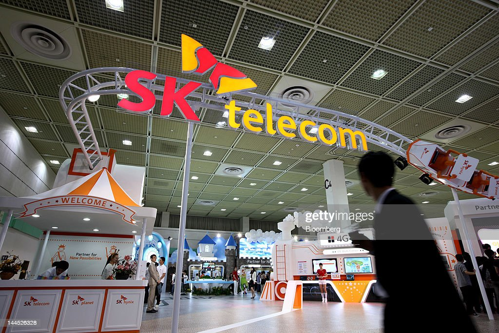 A visitor walks past the SK Telecom Co. booth at the World IT Show 2012 in Seoul, South Korea, on Tuesday, May 15, 2012. The show will be held through May 18. Photographer: SeongJoon Cho/Bloomberg via Getty Images