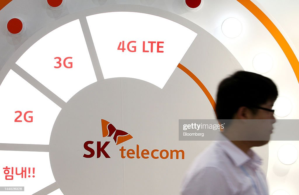 A visitor walks past the SK Telecom Co. logo displayed at the company's booth at the World IT Show 2012 in Seoul, South Korea, on Tuesday, May 15, 2012. The show will be held through May 18. Photographer: SeongJoon Cho/Bloomberg via Getty Images