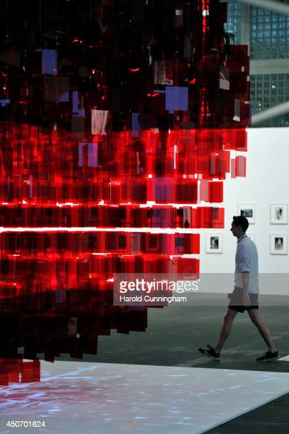 A visitor walks past to the artwork 'Continuel Mobile Sphere rouge' by Michelangelo Pistoletto in the Unlimited section of Art Basel on June 16 2014...