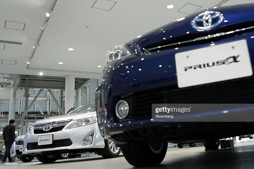 A visitor walks past Toyota Motor Corp. Sai, from left, Camry, Prius Alpha hybrid vehicles displayed at the company's showroom in Tokyo, Japan, on Tuesday, Nov. 5, 2013. Toyota, the world's largest automaker, will probably deliver record semiannual profit when it reports earnings tomorrow, as the weaker yen bolsters the value of Japanese cars sold overseas. Photographer: Kiyoshi Ota/Bloomberg via Getty Images