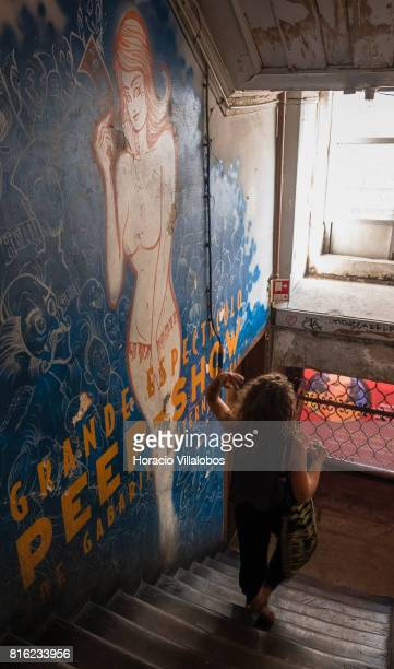 A visitor walks past wall painting at the staircase evoking peepshows of former times at 'Pensao Amor' on July 14 2017 in Lisbon Portugal 'Pensao...