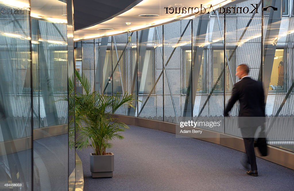 A visitor walks through a glass corridor in the European Parliament building on December 4, 2013 in Brussels, Belgium. The legislative body also has representation in Strasbourg and Brussels.