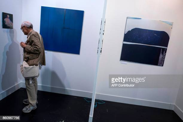 A visitor walks through the exhibition titled 'Unhuman Art in the Age of AI' featuring artwork produced by the AICAN algorithm which autonomously...