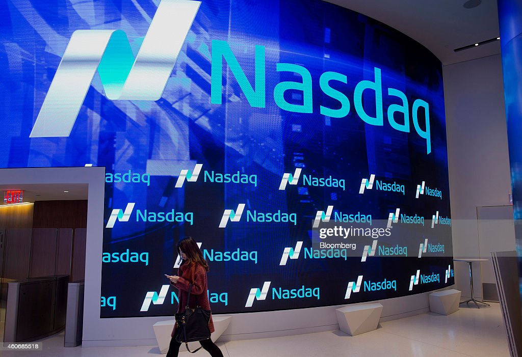A visitor walks through the new lobby of the Nasdaq MarketSite in New York US on Friday Dec 19 2014 While Nasdaq helped usher in the US stock markets...