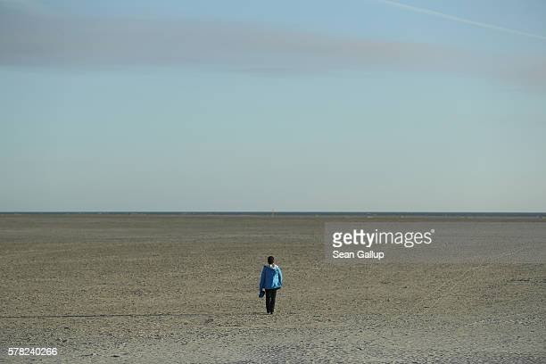 A visitor walks towards the sea on a beach on July 18 2016 at SanktPeterOrding Germany SanktPeterOrding is among the top destinations for vacationers...