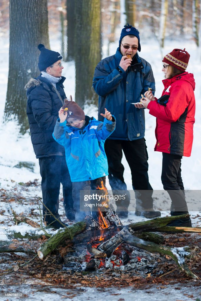 A visitor warm themselves over to a camp fire after choosing and cutting down their Christmas trees in a forest on on December 8, 2012 in Fischbach, Germany. Forestry officials in the state of Saxony officially opened the 2012 Christmas tree season for people who want to retrieve their tree from designated forests rather than just buying it readily cut.