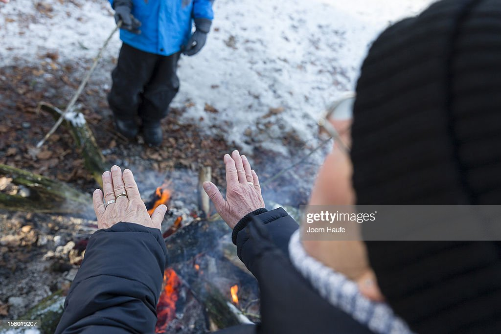 A visitor warms their hands over to a camp fire after choosing and cutting down their Christmas trees in a forest on on December 8, 2012 in Fischbach, Germany. Forestry officials in the state of Saxony officially opened the 2012 Christmas tree season for people who want to retrieve their tree from designated forests rather than just buying it readily cut.