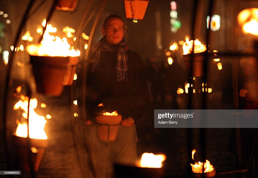 A visitor warms up next to flowerpots full of flames during a presentation by the French fire performers Carabosse as part of celebrations marking the 775th anniversary of the city of Berlin on October 28, 2012 in Berlin, Germany. The settlement of Coelln, which stood opposite Berlin on the Spree river, is first referred to in a document from 1237, and by the beginning of the 14th century Coelln and Berlin joined together to become the region's most important trading center.