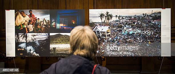 A visitor watches pictures of the World Press Photo exhibition in Amsterdam on April 17 2014 The exposition takes place for the first time in fifteen...