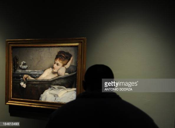 A visitor watches the painting 'Le bain' by French artist Alfred Stevens shown at the Brazil Bank Cultural Centre on October 23 2012 in Rio de...