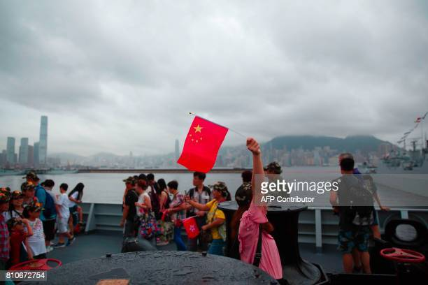 A visitor waves the Chinese national flag on board the Yinchuan a People's Liberation Army Navy Type 052D destroyer as the Hong Kong skyline is seen...