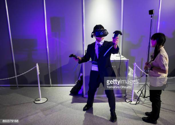 A visitor wearing a an HTC Corp Vive virtual reality headset plays a video game in the Intel Corp booth during the Tokyo Game Show 2017 at Makuhari...