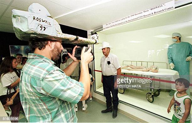 A visitor wearing a homemade hat takes pictures of a scene displayed in what is being called the 'International UFO Museum and Research Center' in...