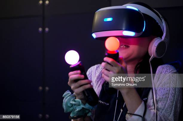 A visitor wearing a PlayStation VR headset plays a video game in the Sony Interactive Entertainment Inc booth during the Tokyo Game Show 2017 at...