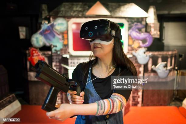 A visitor wearing a VR headset plays the Ghost Attackers VR virtual reality video game at the VR Park Tokyo on May 12 2017 in Tokyo Japan The VR Park...