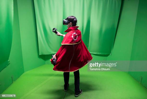 A visitor wearing an HTC Corp Vive VR headset plays the Circle of Saviors Beginners virtual reality video game at the VR Park Tokyo on May 12 2017 in...