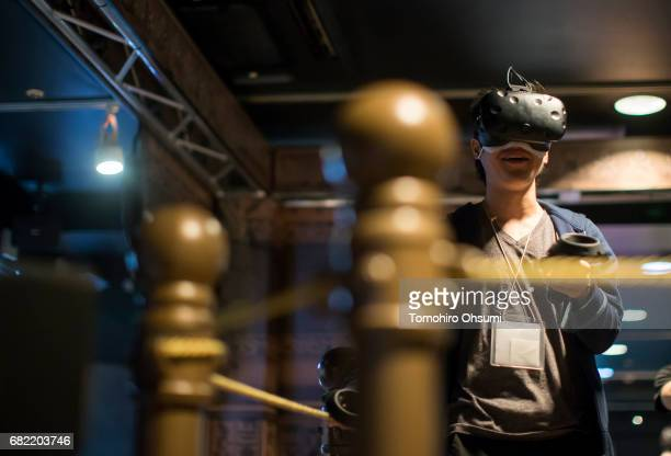 A visitor wearing an HTC Corp Vive VR headset plays the Salomon's Carpet VR virtual reality video game at the VR Park Tokyo on May 12 2017 in Tokyo...