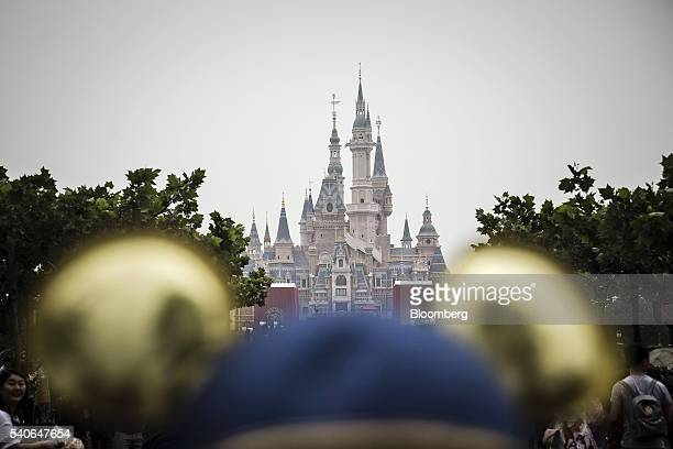 A visitor wearing gold Mickey Mouse ears stands in front of the Enchanted Storybook Castle during the opening day of Walt Disney Co's Shanghai Disney...