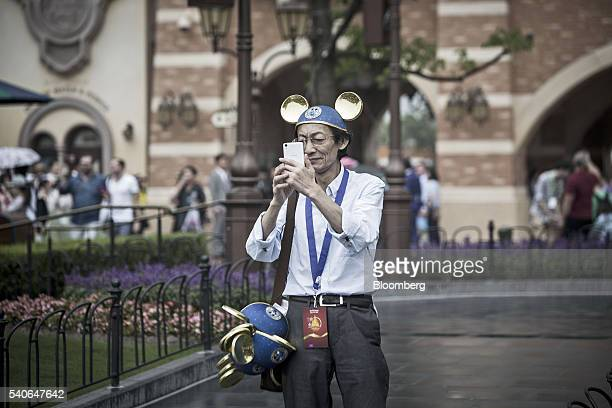 A visitor wearing gold Mickey Mouse ears takes photographs with his smartphone during the opening day of Walt Disney Co's Shanghai Disney Resort in...