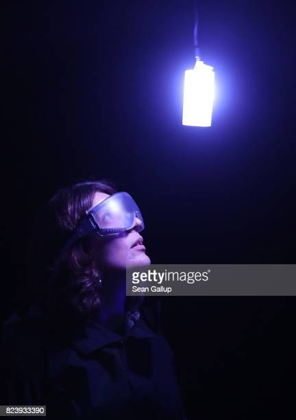 A visitor wearing milky goggles and devices strapped to her body that emit light in different colors and have haptic engines pauses as she walks...