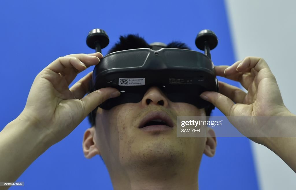 A visitor wears a China's Ehang designed visual reality (VR) Ghostdrone headset linked to a drone during the annual Computex computer exhibition in Taipei on May 31, 2016. More then 5,000 booths from thirty countries take part in COMPUTEX Show between May 31 to June 4. / AFP / SAM YEH