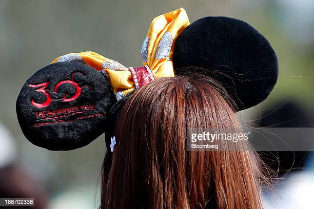 A visitor wears a headband featuring the ears of the Walt Disney Co character Minnie Mouse during 30th anniversary celebrations of Tokyo Disneyland...