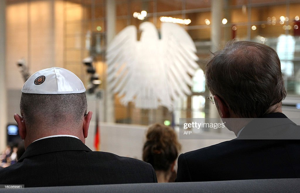 A visitor wears a kippah as he listens to speeches at the German lower house of Parliament Bundestag, in Berlin on January 30, 2013 during a memorial held by deputies for the victims of the Nazi regime, and the anniversary of the liberation of Auschwitz concentration camp on January 27, 1945. Since the date fell on a Sunday this year, the event was held later, on the day marking 80 years since Adolf Hitler became chancellor. BERRY
