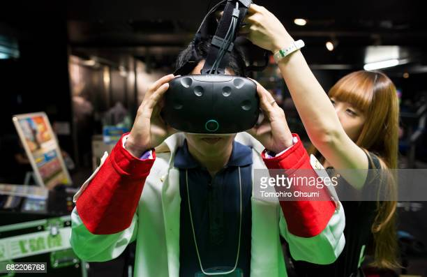 A visitor wears an HTC Corp Vive VR headset as he plays the Circle of Saviors Beginners virtual reality video game at the VR Park Tokyo on May 12...