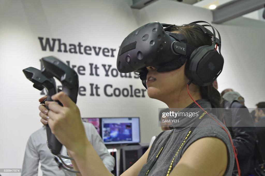 A visitor wears the HTC Vive visual reality (VR) headset during the annual Computex computer exhibition in Taipei on May 31, 2016. More then 5,000 booths from thirty countries take part in COMPUTEX Show between May 31 to June 4. / AFP / SAM YEH