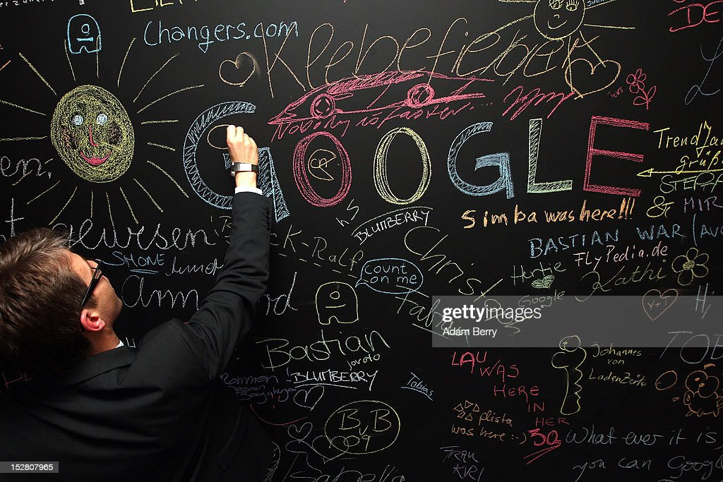 A visitor writes on a chalkboard on September 26 2012 at the official opening party of the Google offices in Berlin Germany Although the American...