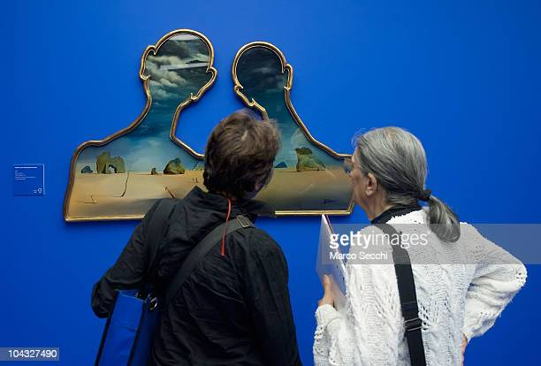 Visitors admire 'A couple with their heads full of clouds' oil painting by Salvador Dali at the Exhibition preview at Palazzo Reale on September 21...