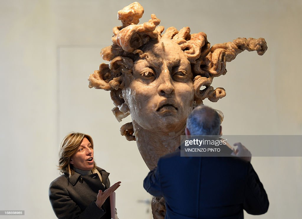 Visitors admire a polyester resin and seeds of amaranth sculpture entitled 'Cabeza de Amaranto' by Mexican artist Javier Marin during the opening of his 'De 3 en 3' exhibition in the Rome's Macro Testaccio museum on December 19, 2012. 'De 3 en 3' is running from December 20 to February 2, 2013.