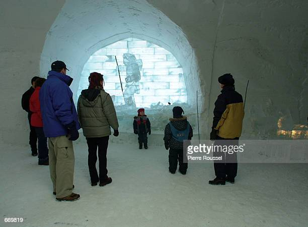Visitors admire an ice sculture depicting an inuit hunter that incorporates real artifacts in one of the two art galleries of the Ice Hotel...